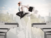 Energetic business man jumping over a bridge with gap Royalty Free Stock Photos