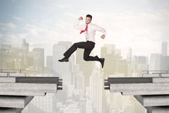 Energetic business man jumping over a bridge with gap Stock Images