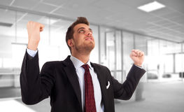 Energetic businessman with arms raised. Stock Image