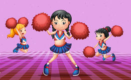 Energetic cheerdancers with red pompoms Royalty Free Stock Images