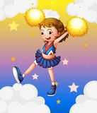 An energetic cheerleader with yellow pompoms Royalty Free Stock Photo