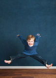 Energetic Child. A happy young boy with lots of energy!  The child is jumping up and smiling at the camera.  Wood floor and blue wall/shirt Royalty Free Stock Images