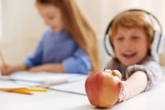 Energetic clever kid taking an apple Royalty Free Stock Photos