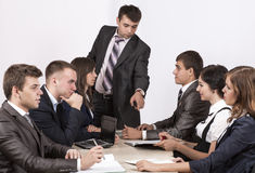 Energetic corporate manager instructs his team. Six people sit around the table covered by paperwork Royalty Free Stock Photos