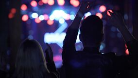 Energetic couple dancing and waving hands at cool music festival in night club. Stock footage stock video