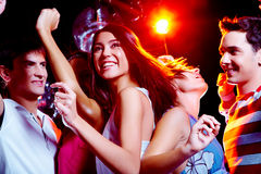 Energetic dance. Photo of energetic girl dancing in the night club with her friends on background royalty free stock photography