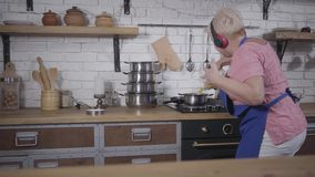 Energetic dance of mature caucasian woman in headphones cooking at the kitchen. Funny senior lady pouring pasta into