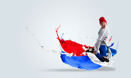 Energetic dancer. Young guy dancer in jump among color splashes Royalty Free Stock Photography