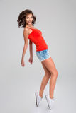Energetic dancing young woman in motion. Isolated royalty free stock image