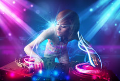 Energetic Dj girl mixing music with powerful light effects. Dj girl mixing music with powerful light effects Royalty Free Stock Image
