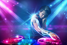 Energetic Dj mixing music with powerful light effects. Young energetic Dj mixing music with powerful light effects Stock Photography