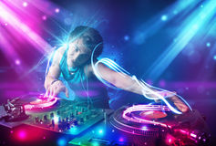 Energetic Dj mixing music with powerful light effects. Young energetic Dj mixing music with powerful light effects Stock Photo