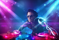 Energetic Dj mixing music with powerful light effects Royalty Free Stock Photography