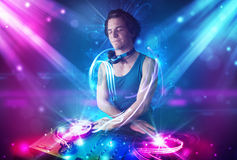 Energetic Dj mixing music with powerful light effects Stock Photography