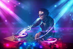 Energetic Dj mixing music with powerful light effects Stock Photos