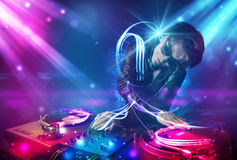 Energetic Dj mixing music with powerful light effects. Young energetic Dj mixing music with powerful light effects Royalty Free Stock Image
