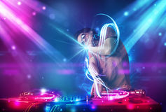 Energetic Dj mixing music with powerful light effects. Young energetic Dj mixing music with powerful light effects Royalty Free Stock Photography