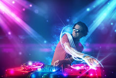 Energetic Dj mixing music with powerful light effects. Young energetic Dj mixing music with powerful light effects Stock Images