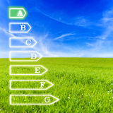 Energetic efficiency. Scale of seven levels of energetic efficiency on virtual screen with beautiful green meadow and blue sky for background. Emphasis on a royalty free stock photography