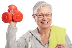 Energetic elderly woman with dumbbells smiling. Energetic elderly woman holding dumbbells, smiling stock photography