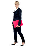 Energetic employee walking with her clipboard Royalty Free Stock Photography