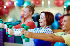 Energetic exercise. Energetic females stretching arms while exercising with dumbbells royalty free stock photo