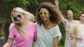 Energetic female couple dancing, smiling for camera, enjoying picnic in park. Stock footage stock video footage