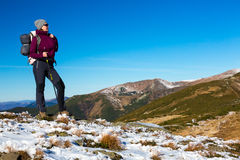 Energetic Female Hiker Staying on Snowy Terrain and Observing Scenic Mountain View Stock Image