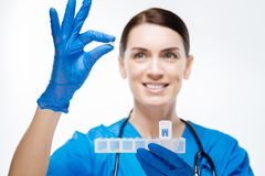 Energetic female lab assistant working with container for medication. Right regimen. Vigorous cute female lab assistant  looking at pill while smiling  on the Royalty Free Stock Photo