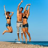 Energetic friends jumping on beach. Stock Image