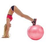 Energetic girl doing handstand on fitness ball Royalty Free Stock Photography