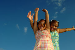 Energetic girls. Two energetic african american girls with arms stretched out across blue sky royalty free stock photos