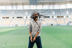 The energetic half-length portrait of the cheerful afro-american teenager shaking the hair on the stadium. Royalty Free Stock Photo