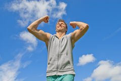 Energetic and happy young man. On blue sky background stock photo