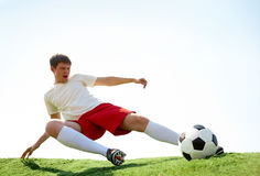 Energetic kick. Portrait of soccer player kicking ball during game Royalty Free Stock Images