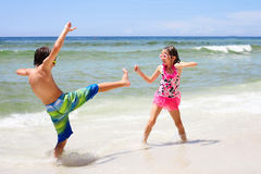 Energetic little children fighting on beach at sea. Energetic little children wearing sunglasses fighting on beach. Siblings or friends having fun at seaside stock image