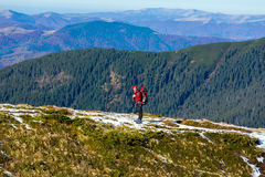 Energetic male Hiker Staying on Trail and Observing Scenic Mountain View. Energetic male Hiker Staying on Snowy Trail and Observing Scenic Mountain View Sporty Royalty Free Stock Photos