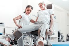 Energetic man exercising and a trainer helping him. Occupational therapy. Joyful energetic old grey-haired men smiling and exercising on a training device while Stock Photo