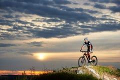 Energetic man in sportswear cycling on rock hill. stock photo