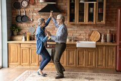 Energetic middle aged family couple dancing in kitchen.