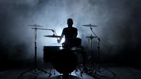 Energetic music in the performance of a professional drummer. Black background. Silhouette stock video