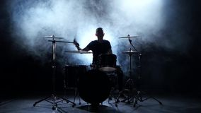 Energetic musician plays good music on drums. Black smoky background. Silhouette stock video footage