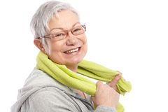 Energetic old woman smiling after workout. Holding towel around neck royalty free stock photos