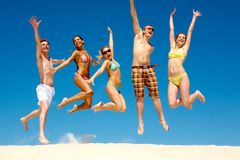 Energetic people. Photo of slim energetic people jumping and screaming at summer stock photos