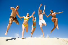 Energetic people. Image of five energetic people jumping at the beach stock images