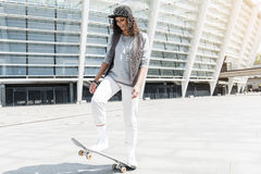 Energetic positive teenager is riding skateboard outdoors Royalty Free Stock Photo