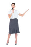 Energetic presenter holding microphone. While posing on white background stock photo