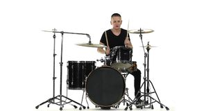 Energetic professional musician plays good music on drums. White background. Slow motion stock video footage