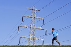 Energetic runner on the under electricity pylon. Netherlands, village of Lent, Municipality, city Nijmegen, a jogger is running on the Waal under high voltage Royalty Free Stock Photography