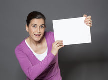 Energetic 30s woman making an announcement in raising a white insert in front of her Stock Image